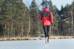 Man under loppet för sportslingaspring i den utomhus- vintern Royaltyfri Bild