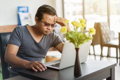 Man under a lot of stress using laptop computer. In cafe Stock Images