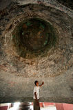 Man under a Mingun bell in Myanmar. Stock Images