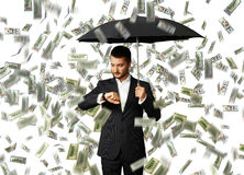 Man under money rain looking at watch Stock Images