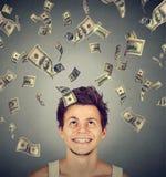 Man under pengarregn som ner faller dollarräkningar Finansiell frihet Arkivbild