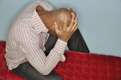 Man under pressure. African American man holding his head in his hands Stock Image