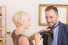 Man under pressure of his wife. Blond lady helping her husband with his tie. Handsome businessman going to work. MArriage concept. Family concept Stock Photos