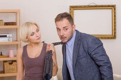 Man under pressure of his wife. Blond lady keeping her husband under pressure. Blond wife keeping her husband`s tie and looking at him. Family concept Stock Photos