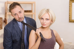 Man under pressure of his wife. Blond lady keeping her husband`s tie and looking at camera. Man under pressure of his wife. Family concept. Wife is head or Royalty Free Stock Photo