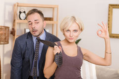 Man under pressure of his wife. Blond lady keeping tie in her hand and showing okay sign demonstrating that her husband under pressure. Family concept Stock Photography