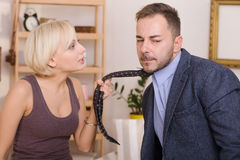 Man under pressure of his wife. Listening to her arguments. Coupe men and women having quarrel. Blond lady keeping his tie. Family concept Stock Photography