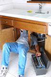 Man Under Sink with Toolbox. Man with body half under sink cabinet and reaching for wrench in toolbox Stock Photo