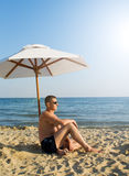 The man under a solar umbrella. On a beach stock image