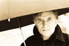 Man under umbrella. A handsome middle-aged man under an umbrella - monochrome Stock Photography