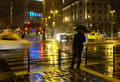 Man under an umbrella in night city Stock Photos