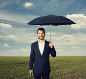 Man under umbrella at outdoor Stock Photo