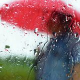 A man under an umbrella in the rain. Drops with and classic autumnal bad weather. Seasonal background with rain. Royalty Free Stock Images