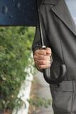 Man under an umbrella in the rain Stock Image