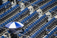 Man under umbrella in a stadium Royalty Free Stock Photo
