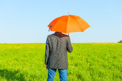 Man under an umbrella on a sunny day Stock Image