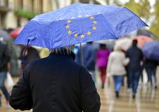 A man under an umbrella with a symbol of the European Union royalty free stock image