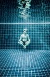 Man under vatten i en simbassäng som ska kopplas av i lotusblommapositioen Royaltyfria Bilder