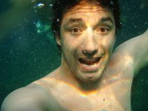 Man under water. Surprised man underwater after he jumped from the rock Royalty Free Stock Photo