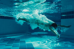 Man under water. Man is jumping into the swimming pool. Man is swimming under water in swimming pool Stock Image