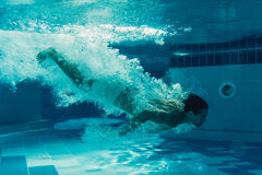 Man under water. Man is jumping into the swimming pool. Man is swimming under water in swimming pool Royalty Free Stock Photos