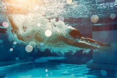 Man under water. Man is jumping into the swimming pool. Man is swimming under water in swimming pool Royalty Free Stock Image