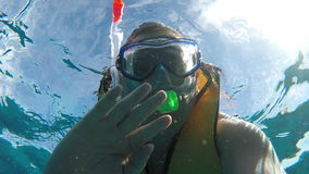 The man under the water waving at the camera. A man in a mask with a tube stock footage