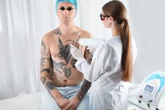 Man undergoing laser tattoo removal procedur. E in salon stock photography