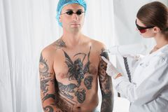 Man undergoing laser tattoo removal procedur. E in salon royalty free stock photos