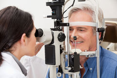 Man Undergoing a Visual Field Test. Optometrist performing visual field test royalty free stock photography