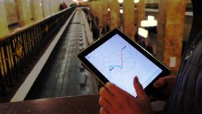 Man in underground examines the metro map. MAR 28, 2018, MOSCOW, RUSSIA: Man in underground examines the metro map using the tablet computer, people passing by stock footage