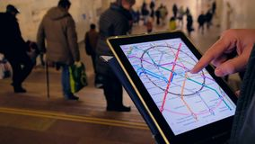Man in underground examines the metro map. MAR 28, 2018, MOSCOW, RUSSIA: Man in underground examines the metro map using the tablet computer, people passing by stock video
