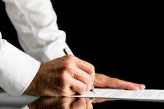 Man underteckning med en penna av ett officiellt dokument Royaltyfri Foto
