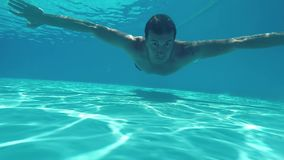 Man underwater. The man dives lifestyle swimming under the water. Happy man swims underwater in swimming pool stock video
