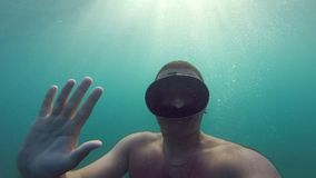 Man underwater in mask for swimming. Guy diving and salutes. Camera is in hand, its self-portrait. Underwater footage stock video footage