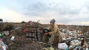 Man unemployed homeless dirty looking food dump. Waste in landfill  social  video stock footage
