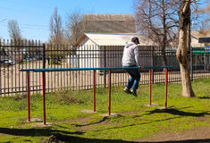The man on the uneven bars, in the park in the open air. Playing sports Stock Images