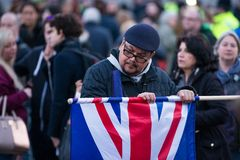 Man Unfolding Union Jack Flag in Trafalgar Square Crowd stock images