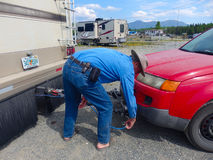 A man unhooking his tow-car at a campground in northern bc stock image