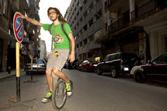 Man on a unicycle, Lebanon. A man on a unicycle holding onto a sign for balance, Lebanon Stock Photo