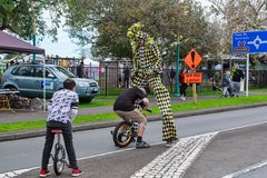 Street entertainment. Unicyclists and a stilt walker royalty free stock photos
