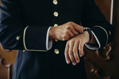 Man in uniform adjusting the time in his watch Stock Images