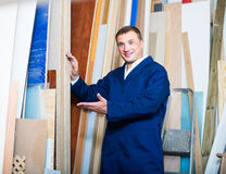 Man in uniform choosing compressed densified wood. Portrait of man in uniform choosing compressed densified wood in picture framing atelier Royalty Free Stock Image