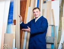 Man in uniform choosing compressed densified wood. Portrait of man in uniform choosing compressed densified wood in picture framing atelier royalty free stock image