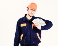 Man in uniform got salary, money for work. Payday concept. Builder earn money, repairman holds banknotes in hand. Mechanic with strict face in hard hat stock image