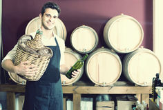 Man in uniform holding large wine bottle with wicker and standin Royalty Free Stock Image
