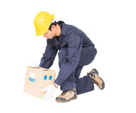 Man in uniform lifting the paper box. Isolated on white background Royalty Free Stock Photo