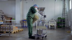 Man in uniform put dried herbal tea into a bucket, tea factory. Worker put dried herbal tea into bucket. The man is working at the tea factory. Prores codec stock video footage