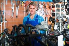 Man in uniform repairing bicycle. Man seller in uniform repairing bicycle in sport hypermarket Royalty Free Stock Images