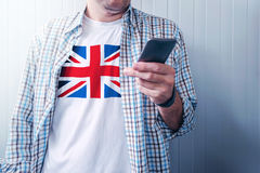 Man with United Kingdom flag on shirt using mobile phone Stock Images